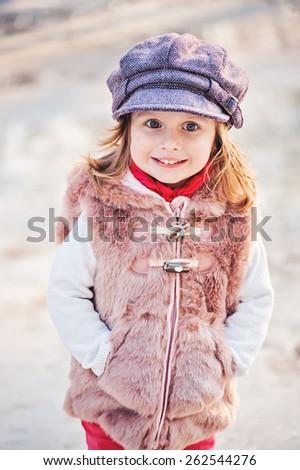spring outdoor vertical portrait of happy toddler child girl in faux fur coat  #262544276