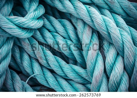 Nautical background. Closeup of an old blue frayed boat rope. Tonned image. Royalty-Free Stock Photo #262573769
