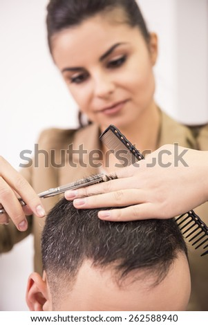 Female hairdresser is cutting hair of man client. #262588940
