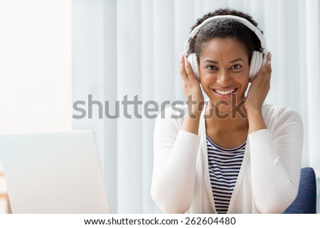 Woman in headphones sitting at desk in office #262604480