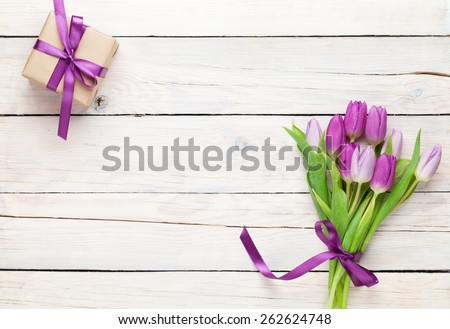 Purple tulips and gift box over wooden table. Top view with copy space #262624748
