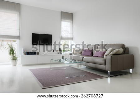 White living room with taupe leather sofa and glass table on carpet #262708727