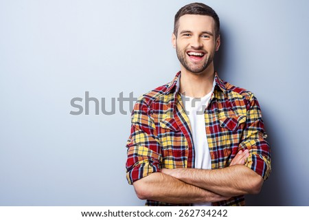 Happy young man. Portrait of handsome young man in casual shirt keeping arms crossed and smiling while standing against grey background Royalty-Free Stock Photo #262734242
