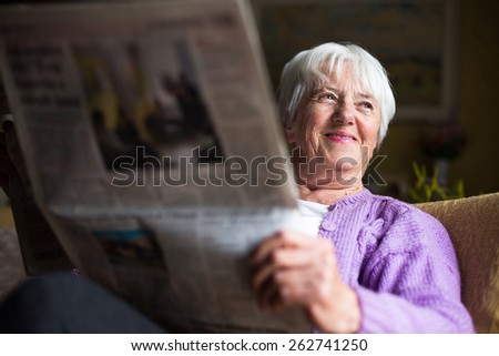 Senior woman reading morning newspaper, sitting in her favorite chair in her living room, looking happy #262741250