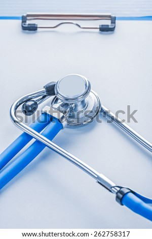 very close up view stethoscope on clipboard with blank sheet of paper medical concept  #262758317