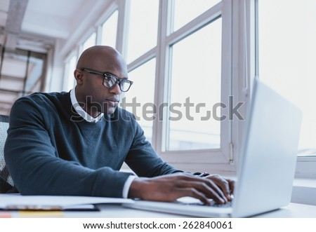 Image of african american businessman working on his laptop. Handsome young man at his desk. #262840061