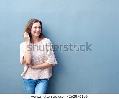 Portrait of an attractive mid adult woman smiling with hand in hair Royalty-Free Stock Photo #262876106