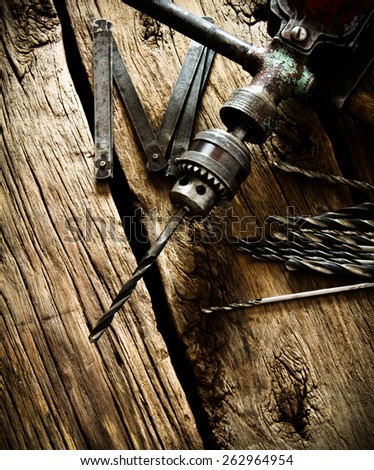 The old working tool. Old drill, a ruler and drills on a wooden background. #262964954
