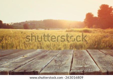 wood board table in front of field of wheat on sunset light. Ready for product display montages  #263016809