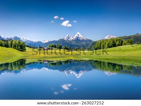Panoramic view of idyllic summer landscape in the Alps with clear mountain lake and fresh green mountain pastures in the background Royalty-Free Stock Photo #263027252