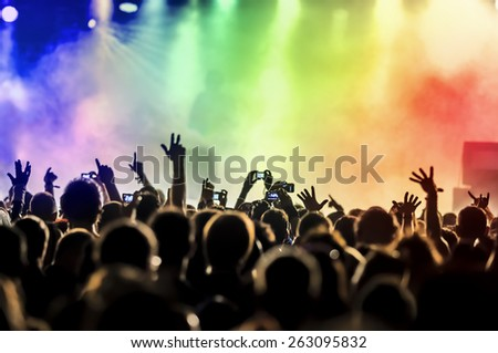 silhouettes of concert crowd in front of bright stage lights #263095832