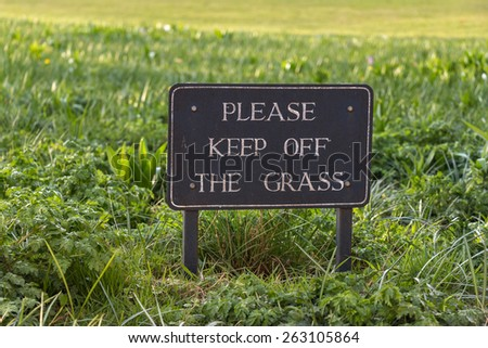 Vintage Caution Sign: Please Keep Off the Grass on grass field background
