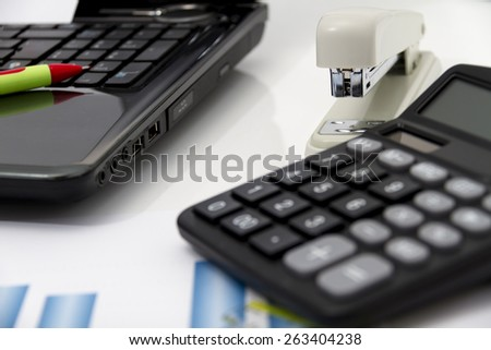 Analyzing business investment charts with calculator and laptop #263404238