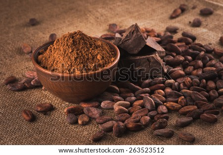 Raw cocoa beans, clay bowl  with cocoa powder, chocolate on sacking #263523512