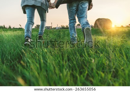 Couple runningon a meadow at the sunset - Boyfriend and girlfriend walking hand in hand - Concepts about love,couple and spring