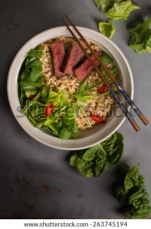 A bowl of Chinese ramen noodles with beef, Chinese cabbage, chili pepper, coriander and green onion, top view #263745194