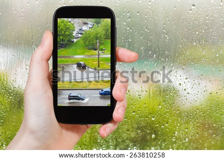 travel concept - tourist takes picture of shower in city from home window on smartphone,