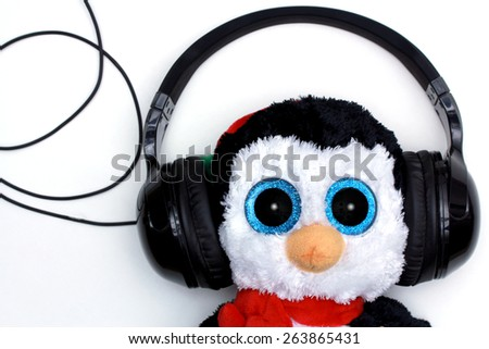 Toy penguin wearing headphones isolated on white
