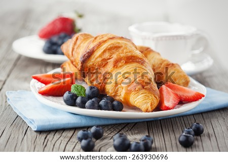 Delicious breakfast with fresh croissants and ripe berries on old wooden background #263930696