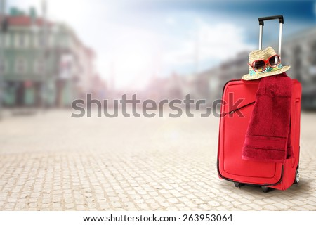 red suitcase with hat in town