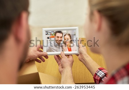 people, family, memories and moving concept - close up of happy couple looking at photo and unpacking things at new home #263953445