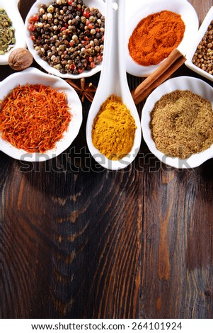 Different kinds of spices in ceramics bowls and spoons on wooden background #264101924
