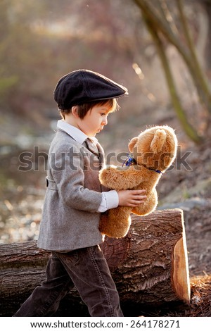 Adorable little boy with his teddy bear friend in the park on sunset, nice back light #264178271