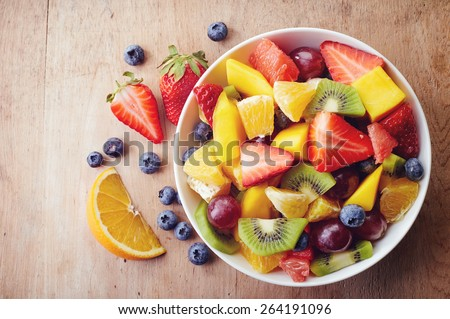 Bowl of healthy fresh fruit salad on wooden background. Top view. Royalty-Free Stock Photo #264191096