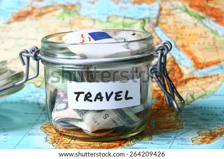 Travel budget - vacation money savings in a glass jar on world map
