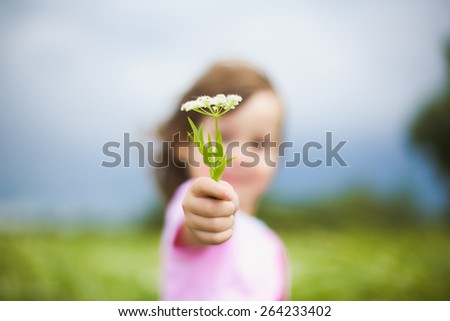 beautiful little girl with wild flowers in green meadow. funny cheerful child playing outdoors.  #264233402