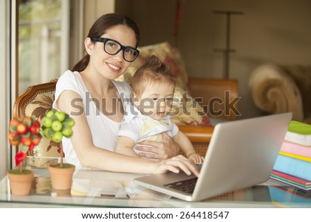 Woman working at home with baby #264418547