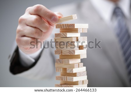 Planning, risk and strategy in business, businessman gambling placing wooden block on a tower Royalty-Free Stock Photo #264466133