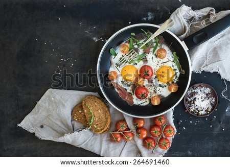 Pan of fried eggs, bacon and cherry-tomatoes with bread on dark table surface, top view #264691460