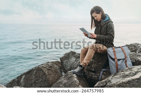 Traveler girl sitting on coast near the sea and working on digital tablet #264757985