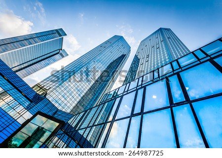 Bottom view of modern skyscrapers in business district against blue sky #264987725