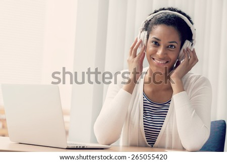 Woman in headphones sitting at desk in office #265055420