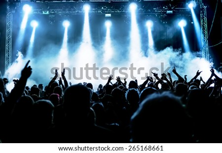 silhouettes of concert crowd in front of bright stage lights #265168661