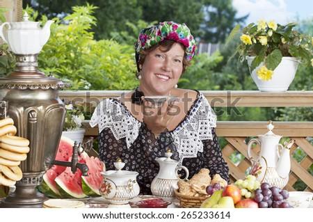 Joyful woman drinking tea outdoors. Kustodiev Russian artist style, beginning of the last century #265233614