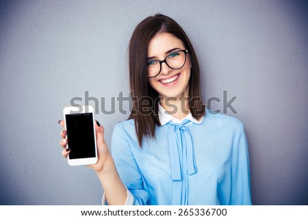 Smiling businesswoman showing blank smartphone screen over gray background. Wearing in blue shirt and glasses. Looking at camera. Royalty-Free Stock Photo #265336700