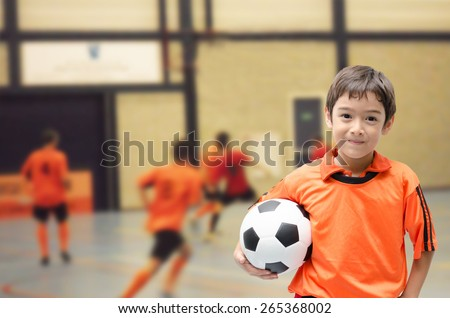 Little boy holding football soccer ball indoor gym Royalty-Free Stock Photo #265368002