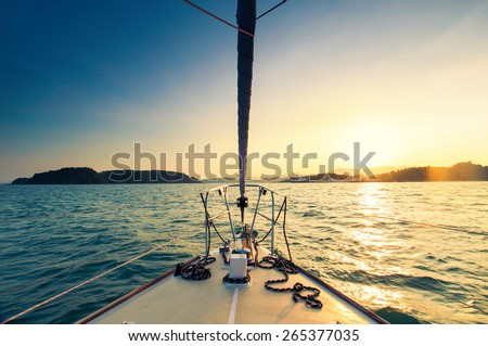 Nose of yacht sailing in the sea at sunset Royalty-Free Stock Photo #265377035