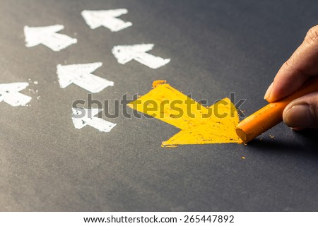 Hand drawing arrow sign in opposite direction from others Royalty-Free Stock Photo #265447892