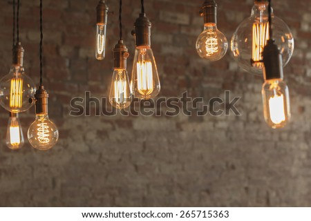 Decorative antique edison style light bulbs against brick wall background #265715363