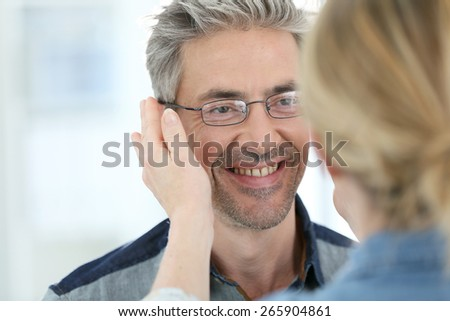 Mature man in optical store trying eyeglasses on #265904861