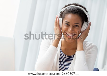 Woman in headphones sitting at desk in office #266060711