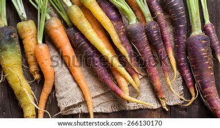 Fresh organic rainbow carrots on a wooden table #266130170