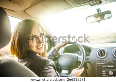 woman in car indoor keeps wheel turning around smiling looking at passengers in back seat idea taxi driver against sunset rays Light shine sky Concept of exam Vehicle - second home the girl #266338391