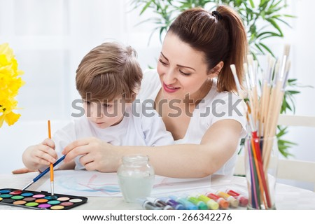 Happy smiling mother and child drawing together with paintbrushes #266342276