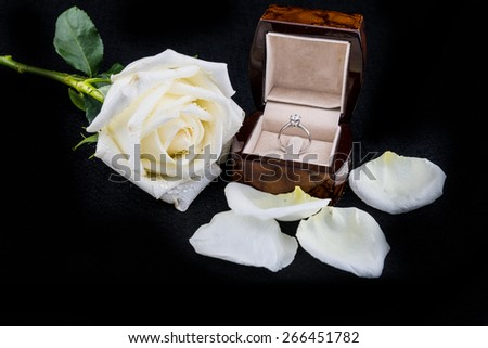 wedding ring in box with white rose flower on black background #266451782
