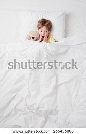 Top view photo of little scared boy under blanket with teddy bear. Concept for children's nightmares #266456888